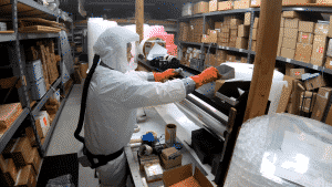 wiping a warehouse shelf with disinfectant
